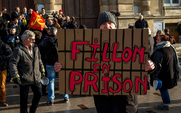 "A man holds a placard reading ""Jail for Fillon"" as people protest aga"